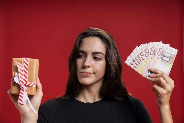 Mulher segurando cartões de crédito e presente