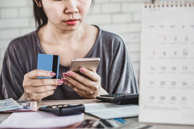 Mulher segurando cartões de crédito e telefone inteligente