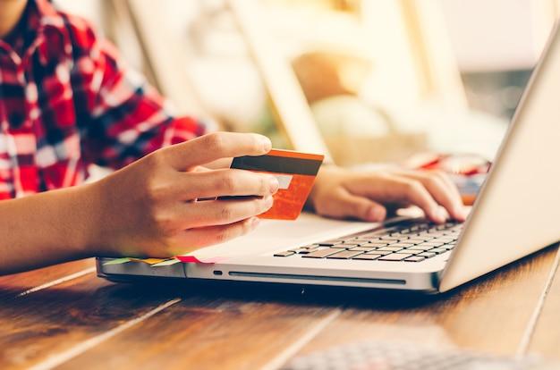 Mulher segurando cartões de crédito e telefones celulares estão agora comprando pela internet pagando
