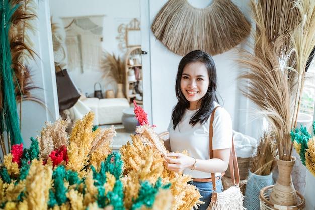 Mulher segurando casualmente plantas artificiais feitas de materiais naturais entre os itens de artesanato na galeria de artesanato