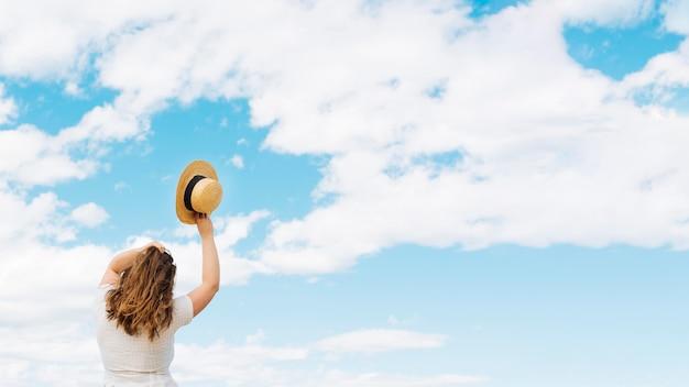 Mulher segurando chapéu admirando nuvens no céu