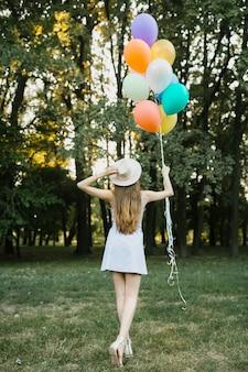 Mulher segurando chapéu e balões ao ar livre