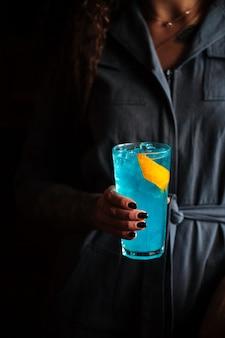 Mulher segurando cocktail azul em uma bola alta com gelo