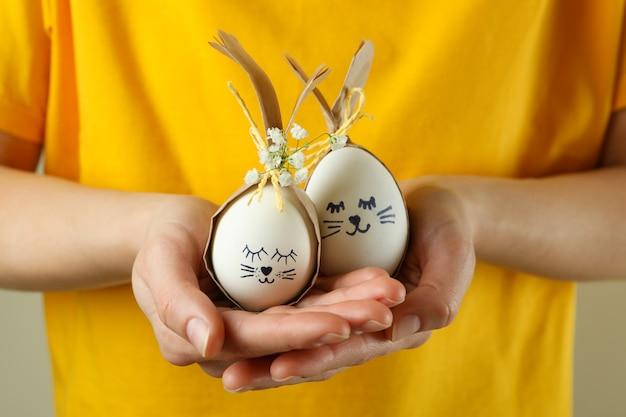 Mulher segurando coelhinhos da páscoa feitos de ovos