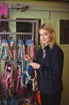 Mulher segurando coleiras de cachorro na loja