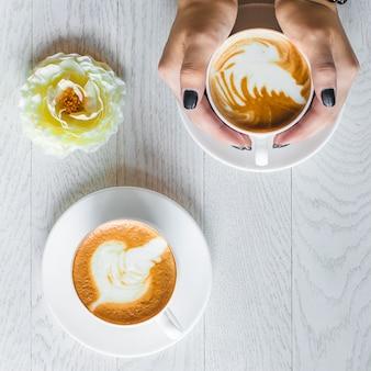 Mulher segurando com as duas mãos um dos copos de café com leite