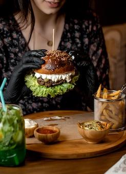 Mulher segurando com luvas pretas, hambúrguer de carne com cogumelos, alface e queijo