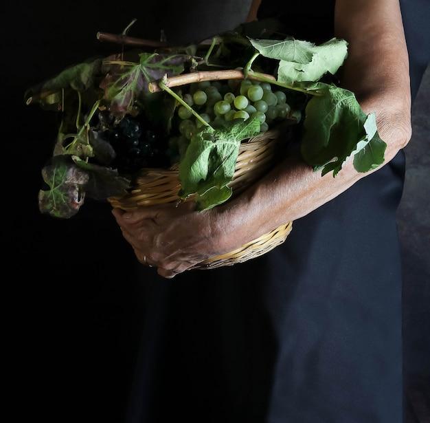 Mulher segurando com um braço uma cesta cheia de uvas