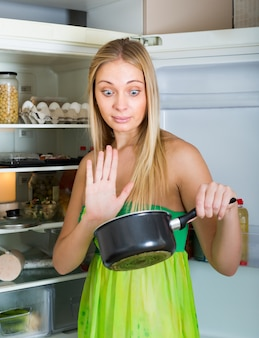 Mulher segurando comida suja perto da geladeira