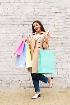 Mulher segurando compras, sacola e cartão de crédito ao ar livre