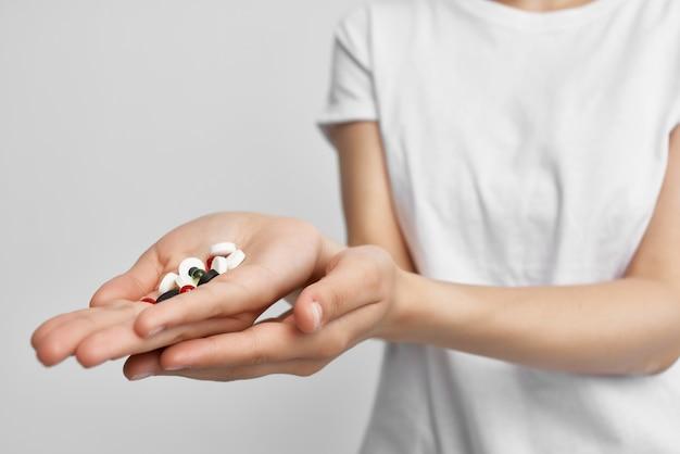 Mulher segurando comprimidos em cápsulas em tratamento com remédio em farmácia de palma