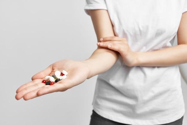 Mulher segurando comprimidos em cápsulas em tratamento de remédios em farmácia de palma