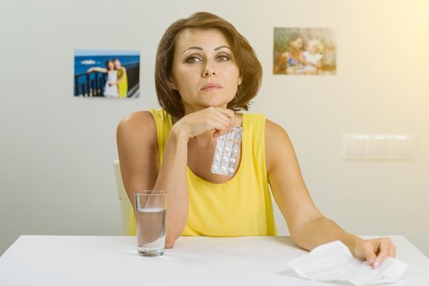 Mulher segurando comprimidos na mão