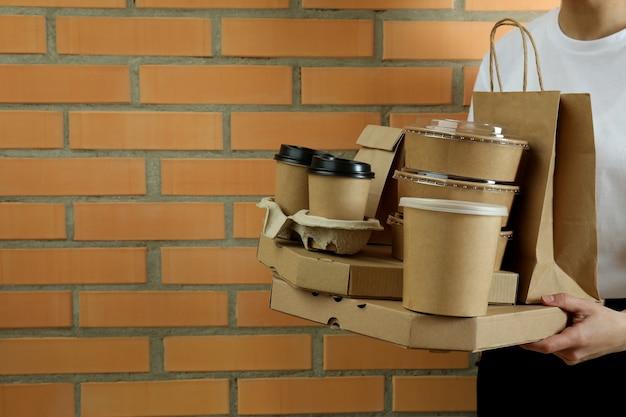 Mulher segurando contêineres de entrega de comida para viagem na parede de tijolos
