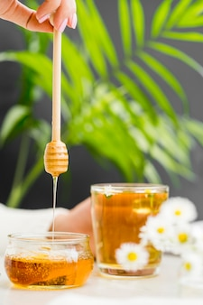 Mulher segurando copo com chá e mel dipper