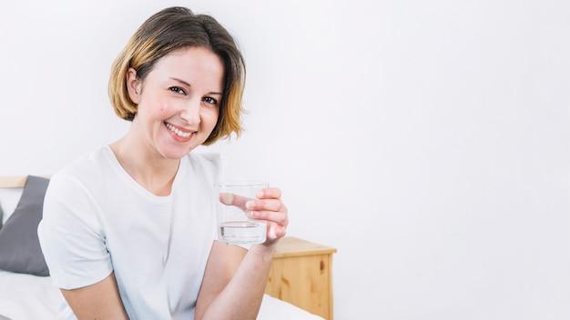 Mulher segurando copo de água