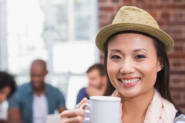 Mulher segurando copo de café com colegas atrás no escritório