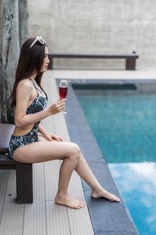 Mulher segurando copo de vinho na piscina