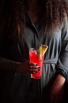 Mulher segurando coquetel vermelho em um copo alto com gelo e abacaxi