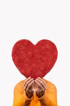 Mulher segurando coração grande entre as mãos, conceito de dia dos namorados