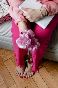 Mulher segurando cravos brancos e rosa