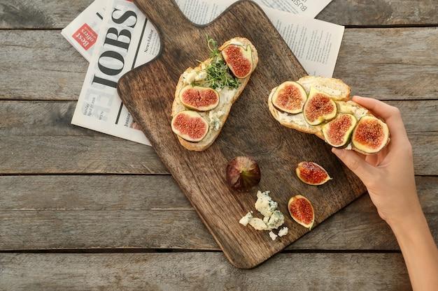 Mulher segurando deliciosos sanduíches com figo na madeira