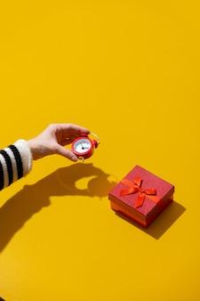Mulher segurando despertador perto de um presente vermelho na superfície amarela