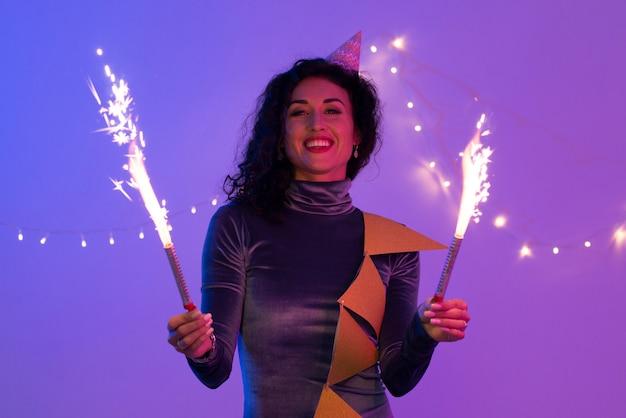 Mulher segurando diamante ardente festivo e se divertindo.