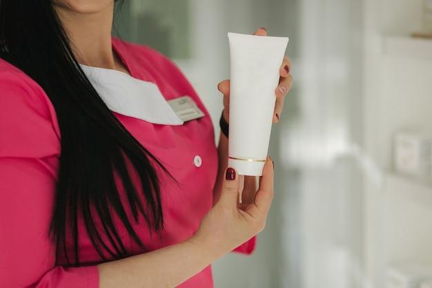 Mulher segurando diferentes cremes médicos em frente a clínica médica