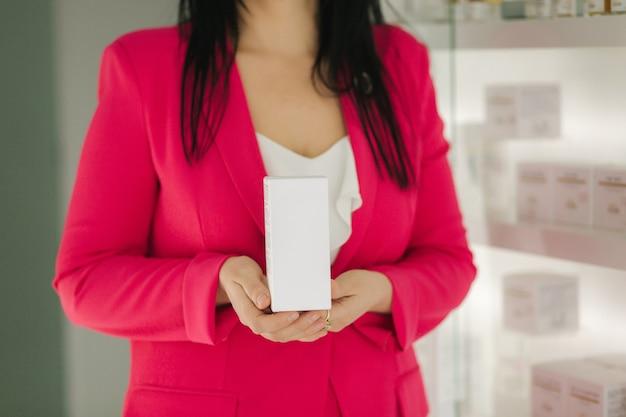 Mulher segurando diferentes produtos cosméticos em frente a clínica médica