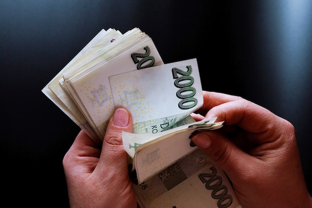 Mulher segurando dinheiro checo em um fundo preto. 2.000 notas.