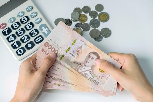 Mulher segurando dinheiro das notas da tailândia com calculadora e moeda