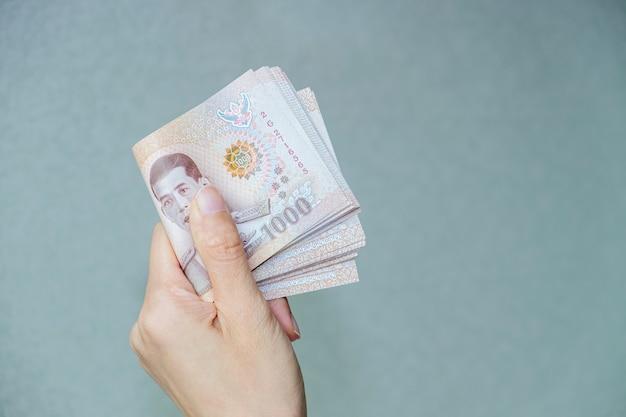 Mulher segurando dinheiro de notas da tailândia com parede cinza