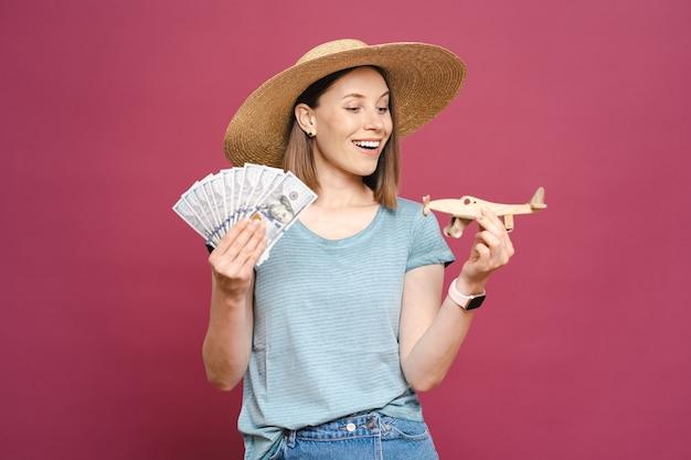 Mulher segurando dinheiro e avião de madeira