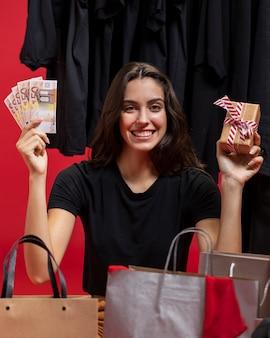 Mulher segurando dinheiro e presente embrulhado