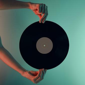 Mulher segurando disco de vinil retrô em foto tonificada de mãos