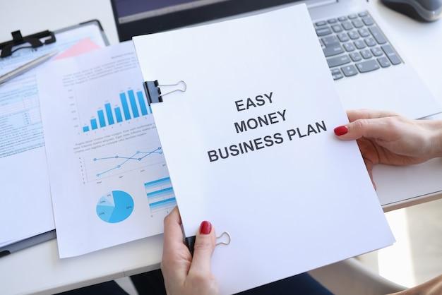 Mulher segurando documentos com plano de negócios de dinheiro fácil título em suas mãos closeup
