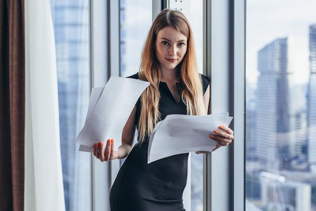 Mulher segurando documentos, olhando papéis, estudando o relatório em pé perto da janela com vista para arranha-céus.