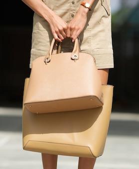 Mulher, segurando, dois, marrom, couro, bolsas