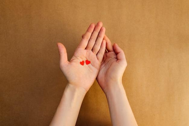 Mulher segurando dois pequenos corações de papel nas palmas das mãos.