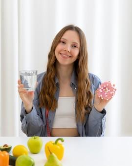 Mulher segurando donut e água