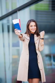 Mulher segurando duas passagens aéreas no exterior passaporte perto do aeroporto