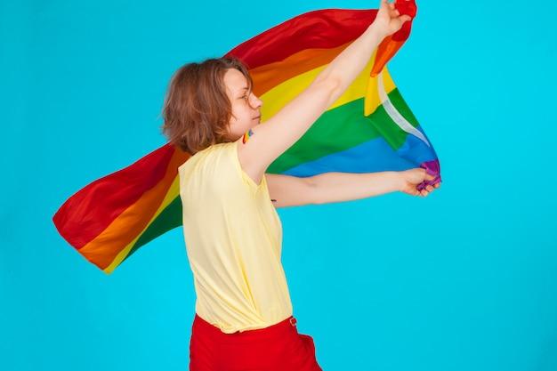 Mulher segurando e acenando uma bandeira lgbt grande