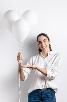 Mulher segurando e apontando para balões