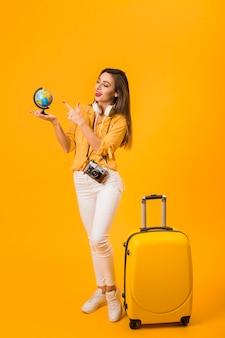 Mulher segurando e apontando para o globo com bagagem ao lado dela