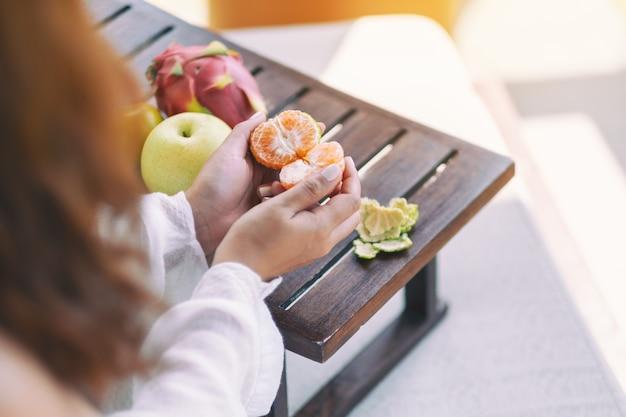 Mulher segurando e descascando uma laranja para comer com pêra e fruta do dragão em uma pequena mesa de madeira