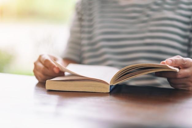 Mulher segurando e lendo um livro de romance vintage na mesa de madeira