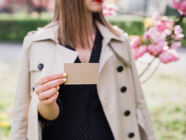 Mulher segurando e mostrando um cartão em branco na natureza ao ar livre