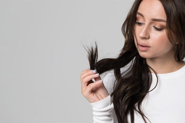 Mulher segurando e olhando para as pontas duplas de seu cabelo comprido danificado.