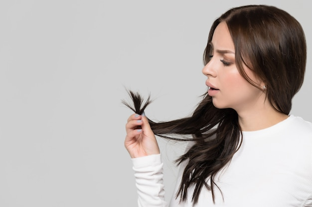 Mulher segurando e olhando para as pontas duplas de seu cabelo danificado.